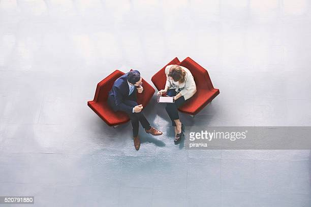 overhead view of two business persons in the lobby - discussion stock pictures, royalty-free photos & images
