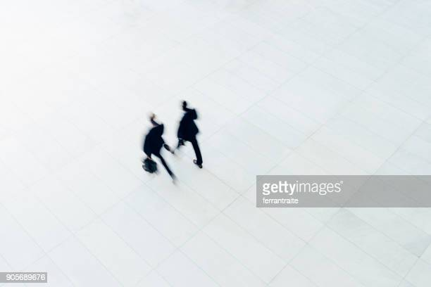 overhead view of two businessman walking - simple stock photos and pictures