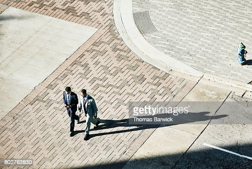 Overhead view of two businessmen in discussion walking across downtown street