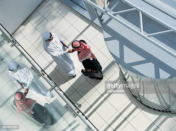 overhead view of two businessmen shaking hands in a lobby by a revolving door - unrecognisable person stock pictures, royalty-free photos & images