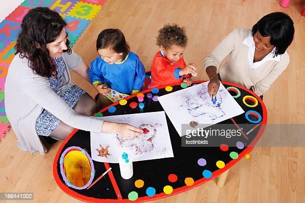 Blickwinkel von zwei Carers tun Kunstwerke mit kleinen Kindern.