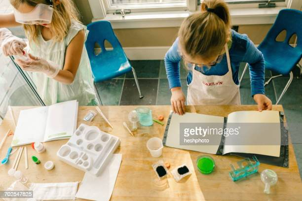 overhead view of two girls doing science experiment, reading chemistry set instructions - heshphoto stockfoto's en -beelden