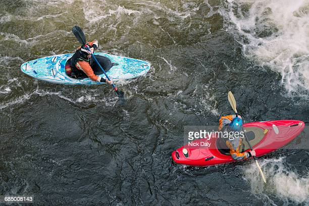 overhead view of two kayakers paddling river dee rapids - water sport stock photos and pictures