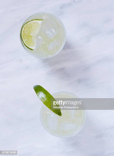 Overhead view of two margaritas on marble table