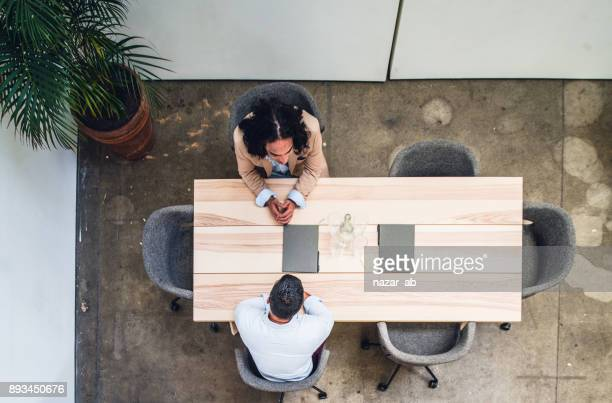 Overhead view of two people in meeting.