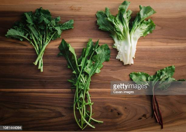 overhead view of various leaf vegetables on wooden table - brassica rapa stock photos and pictures