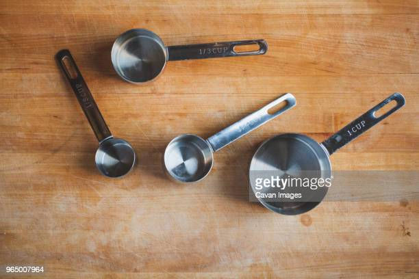 Overhead view of various measuring cups on wooden table