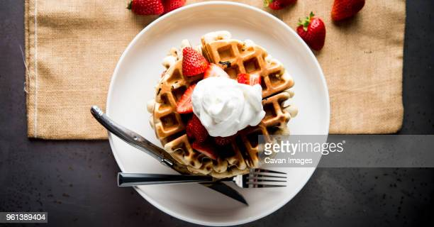 overhead view of waffles garnished with strawberries and whipped cream - waffle stock pictures, royalty-free photos & images