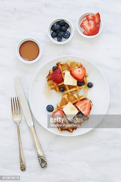 overhead view of waffles with strawberries and blueberries - waffle stock photos and pictures