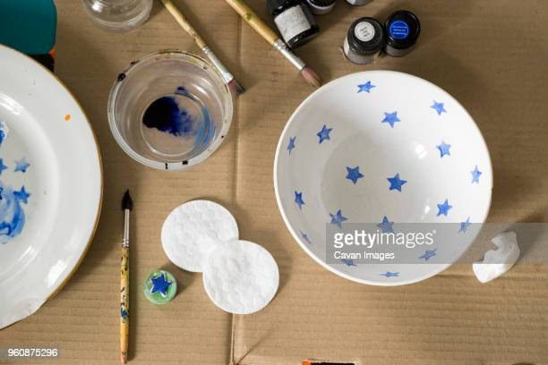Overhead view of watercolor paints and brushes with bowls on cardboard