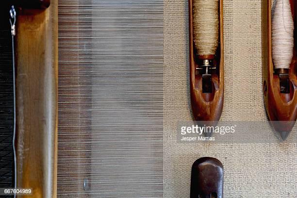 Overhead view of weaving shuttles on loom