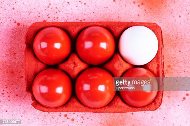 Overhead view of white and red painted easter eggs in carton with splatters on background