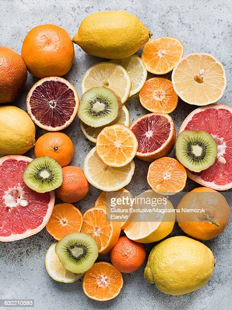 Overhead view of whole and half citrus fruit assortment