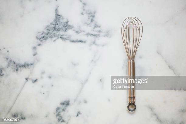 overhead view of wire whisk on marble - wire whisk stock pictures, royalty-free photos & images