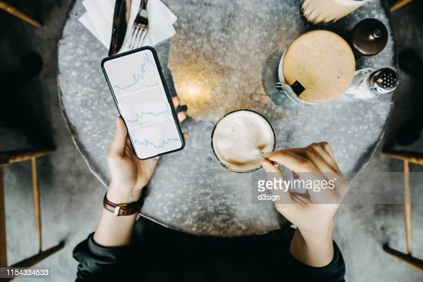 overhead view of woman checking financial trading data on smartphone while drinking coffee in cafe - börsenhandel finanzberuf stock-fotos und bilder