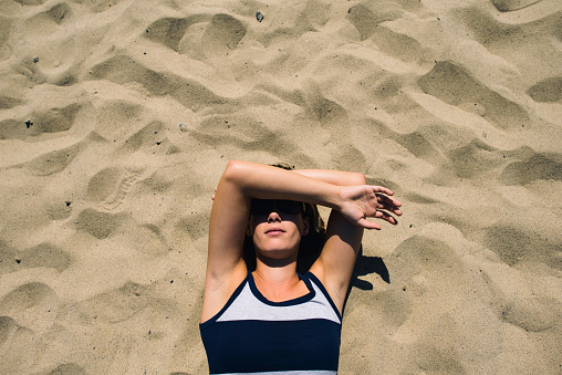 Overhead view of woman covering face while lying on sand during sunny day - gettyimageskorea
