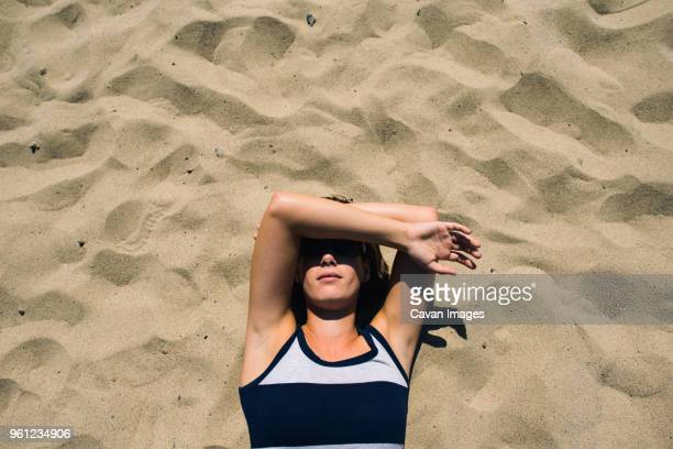 overhead view of woman covering face while lying on sand during sunny day - lying down fotografías e imágenes de stock