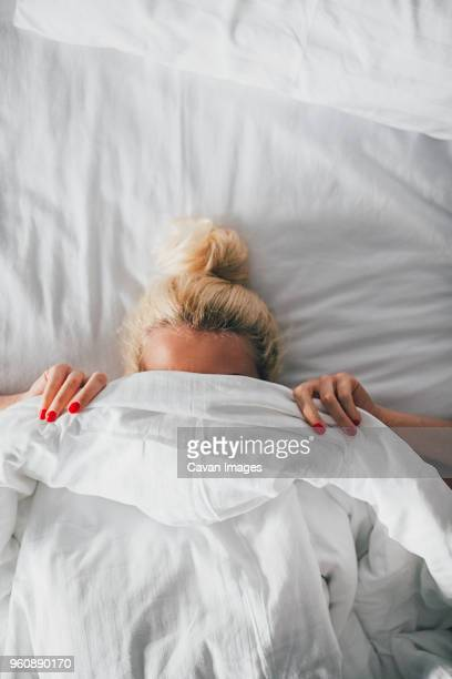 Overhead view of woman covering face with blanket on bed