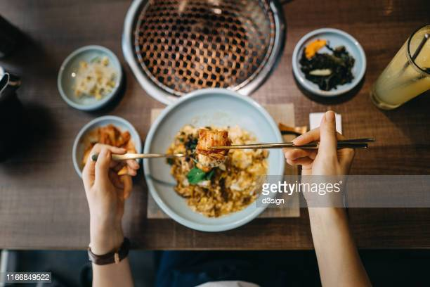overhead view of woman eating korean style beef and scrambled egg rice bowl with kimchee in a korean restaurant - korean culture stock pictures, royalty-free photos & images