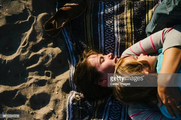 Overhead view of woman embracing daughter while lying on beach towel