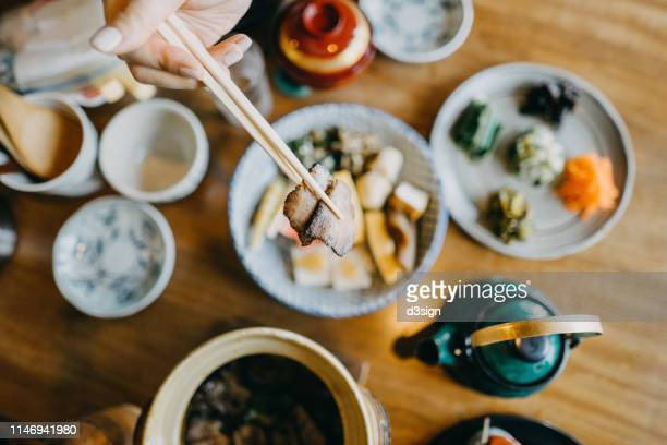 overhead view of woman enjoying delicate japanese cuisine with various side dishes and green tea in the restaurant - tavolo da soggiorno foto e immagini stock