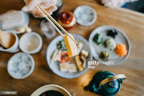 overhead view of woman enjoying delicate japanese cuisine with various side dishes and green tea in the restaurant - フラットレイ ストックフォトと画像