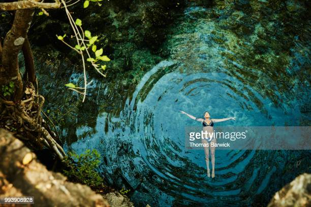 overhead view of woman floating on back in cenote while on vacation - zen like stock pictures, royalty-free photos & images
