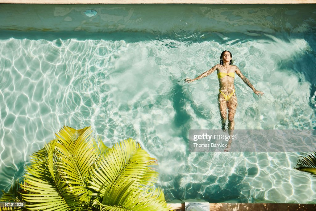 Overhead view of woman floating on her back in pool at outdoor spa : Stock Photo