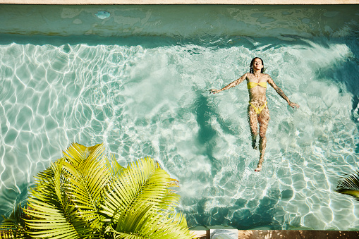 Overhead view of woman floating on her back in pool at outdoor spa - gettyimageskorea