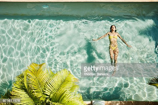 Overhead view of woman floating on her back in pool at outdoor spa