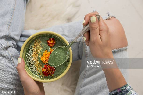 Overhead view of woman holding bowl of food garnished with flowers