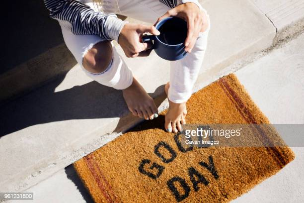 overhead view of woman holding coffee cup while sitting on steps at entrance - human doormat foto e immagini stock