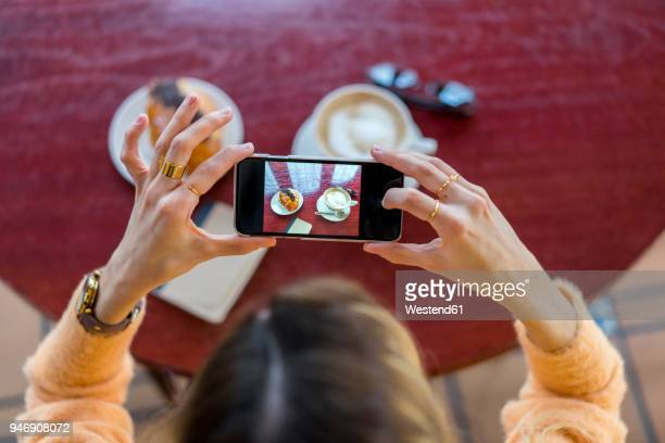 overhead view of woman in a cafe taking cell phone picture - influencers stock pictures, royalty-free photos & images
