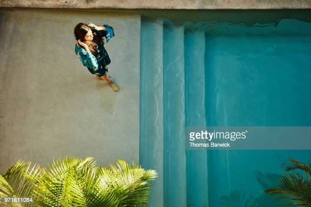 Overhead view of woman in robe standing on top step of hotel pool