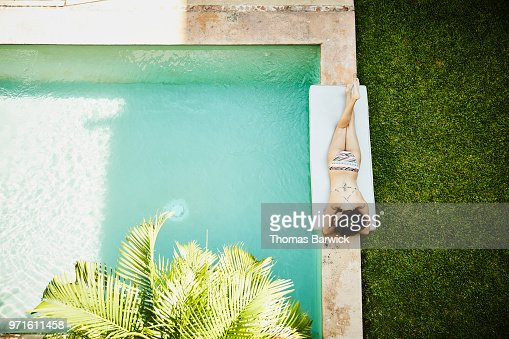 Overhead view of woman lying next to pool in courtyard of outdoor spa