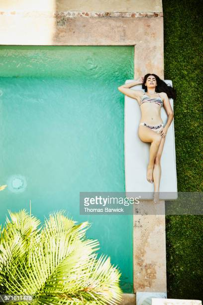 Overhead view of woman lying on her back next to pool in courtyard of outdoor spa