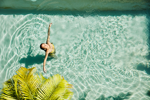 Overhead view of woman relaxing in pool at outdoor spa - gettyimageskorea