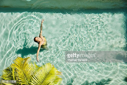 Overhead view of woman relaxing in pool at outdoor spa