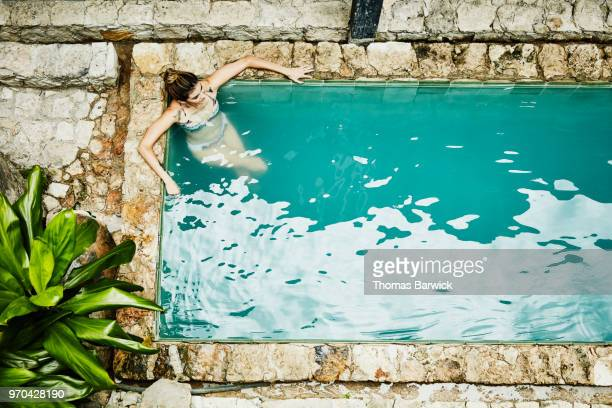 Overhead view of woman relaxing in pool in courtyard of boutique hotel