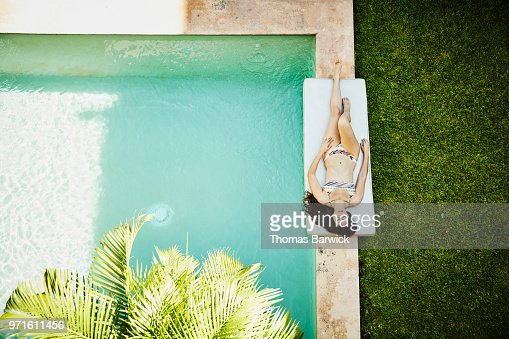 Overhead view of woman relaxing next to pool in courtyard of outdoor spa