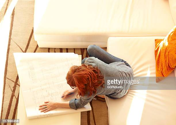 overhead view of woman reviewing architecture plans at home - feng shui stock photos and pictures