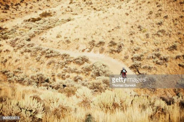 Overhead view of woman riding dirt bike on desert road on summer afternoon