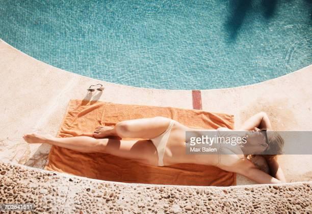 Overhead view of woman sunbathing poolside, Torreblanca, Fuengirola, Spain