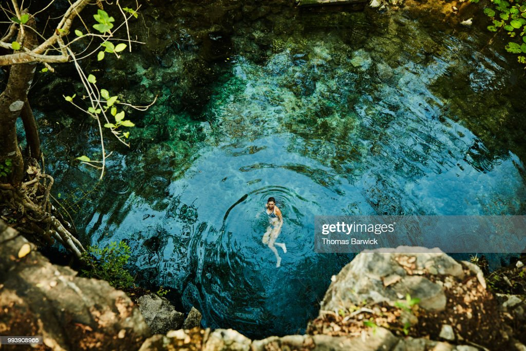 Overhead view of woman swimming in cenote while on vacation : Stock Photo