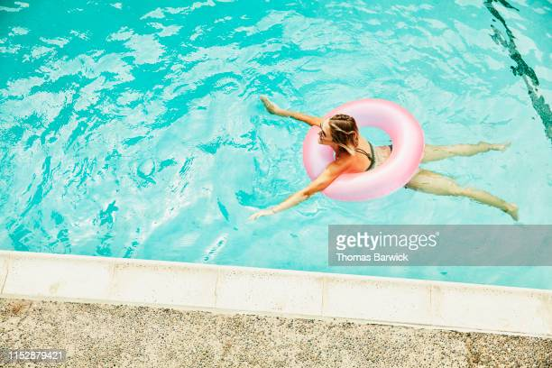 overhead view of woman swimming in hotel pool with pink inflatable ring - piscina pubblica all'aperto foto e immagini stock