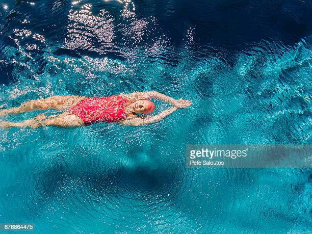 overhead view of woman swimming on back in swimming pool - bainbridge island stock pictures, royalty-free photos & images