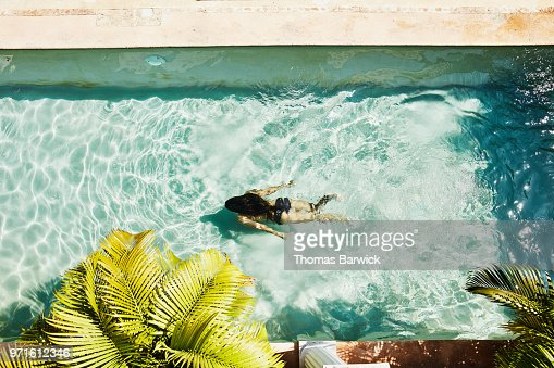 Overhead view of woman swimming underwater in outdoor pool at spa