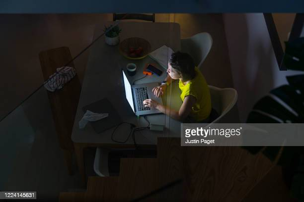 overhead view of woman using her laptop at night - makeshift stock pictures, royalty-free photos & images