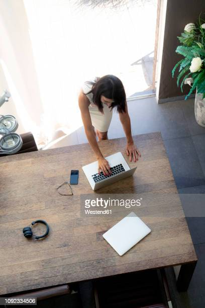 overhead view of woman using laptop at desk - red dress fotografías e imágenes de stock