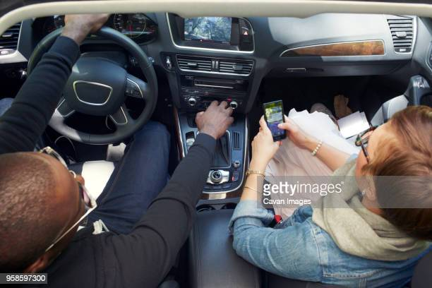Overhead view of woman using smart phone while traveling with boyfriend in car
